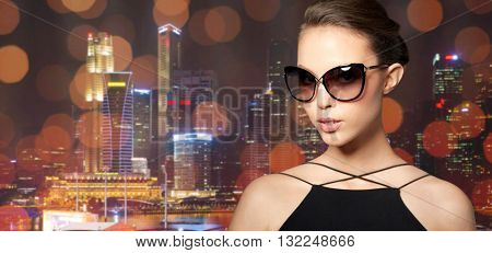 accessories, eyewear, fashion, people and luxury concept - beautiful young woman in elegant black sunglasses over night city lights background