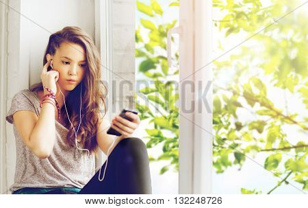 people, technology and teens concept - sad pretty teenage girl sitting on windowsill with smartphone and earphones listening to music