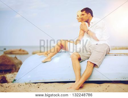 summer holidays and dating concept - couple sitting and embracing at sea side