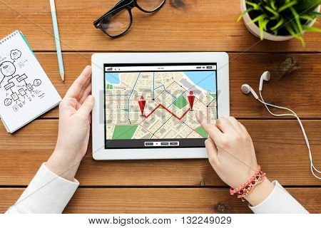 business, technology, people and navigation concept - close up of woman with gps navigator map on tablet pc computer screen on wooden table