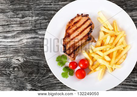 grilled pork chops on a white dish with french fries cherry tomatoes cilantro leaves on a wooden table blank space left top view