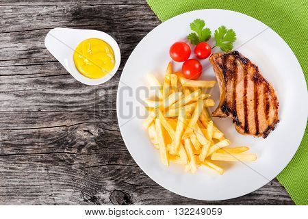grilled pork chops on a white dish with french fries cherry tomatoes cilantro leaves and mustard on a wooden table blank space left top view