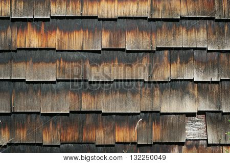 Wooden siding showing the effects of time and weather. Shades of brown.