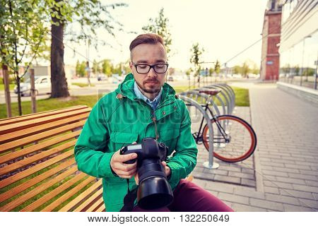 people, photography, technology, leisure and lifestyle - young hipster man holding and looking to digital camera with big lens on city street