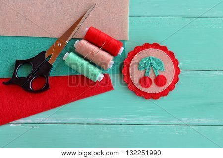 Cute felt brooch with berries. Set for needlework -- thread, felt, scissors, needle. Easy hand sewing project for kids. Creative home idea. Crafts sew. Wooden background