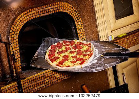 Fresh original Italian pizza on a shovel is putting into a traditional wood-fired stone oven.