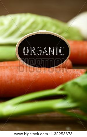 closeup of a black signboard with the text organic placed on a pile of some different raw vegetables, such as carrots, parsnips, turnips, cabbage and celery, on a rustic wooden table