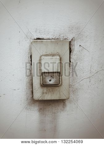 Old and dirty doorbell on concrete wall background vintage effect