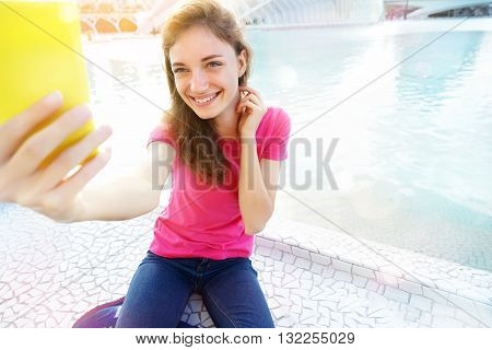 Tourist woman taking mobile phone selfie picture at City of Arts and Sciences. Summer travel vacation in Valencia Spain