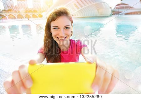 Girl holding Yellow smartphone for self-portrait photo with view of Hemisferic in City of Arts and Sciences. Summer travel vacation in Valencia Spain