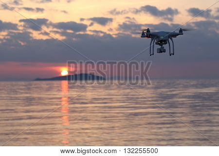 KAGAWA, JAPAN - MAY 30, 2016: Remote controlled drone Dji Phantom 3 equipped with high resolution video camera flying above the sea against a sunset sky.