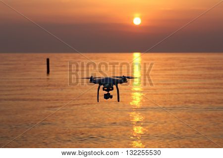 KAGAWA, JAPAN - MAY 31, 2016: Remote controlled drone Dji Phantom 3 equipped with high resolution video camera flying above the sea against a sunset sky.