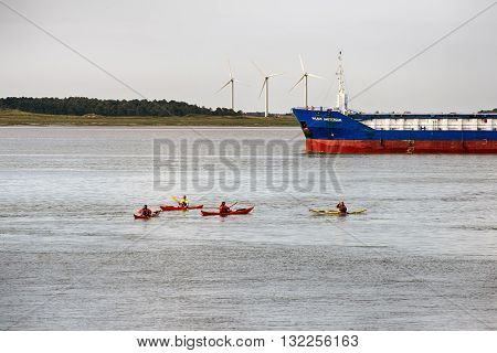 ESBJERG - MAY 28: Cargo boat close to Esbjerg harbor. Kayaks on tour and windmills on Fanoe Island in the background on May 28 2016 in Denmark.