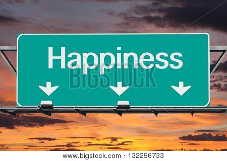 Road to happiness freeway sign with sunrise sky.