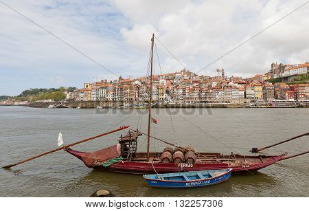 PORTO PORTUGAL - MAY 25 2016: Traditional Rabelo boat (used for port wine transportation) on Douro River in Porto Portugal. Historical part of Porto city (UNESCO site) at the background