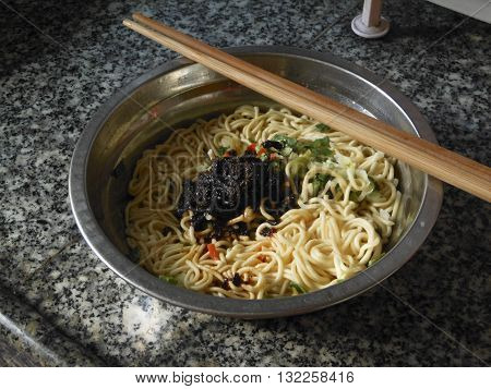 Cooking lo mein noodles after dredging before stirring oyster sauce and seasonings.