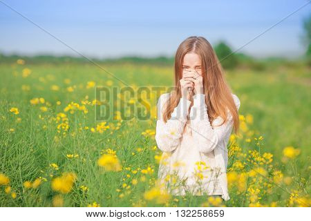 Pollen allergy girl sneezing in a rapeseed field of flowers