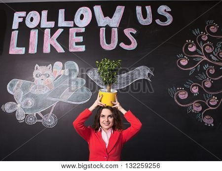 Portrait of beautiful businesswoman holding flower pot on her head. Happy lady in red business jacket looking at camera over black background.