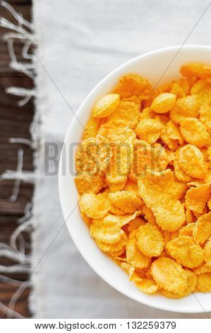 Tasty corn flakes in bowl. Rustic wooden background with homespun napkin. Healthy crispy breakfast snack. Top view flat lay.