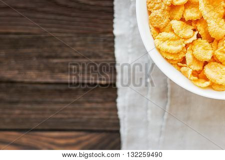 Tasty corn flakes in bowl on homespun napkin. Rustic wooden background. Healthy crispy breakfast snack. Place for text. Top view flat lay.