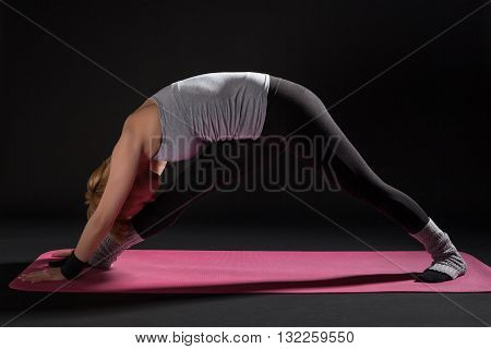 Young woman practicing yoga, Parsvotanasana / Intense Side Stretch Pose