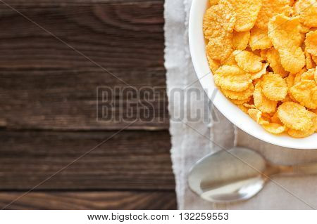 Tasty corn flakes in bowl. Rustic wooden background with homespun napkin. Healthy crispy breakfast snack. Place for text. Top view flat lay.