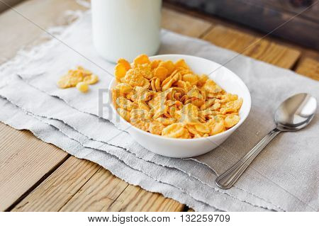 Tasty corn flakes in bowl with bottle of milk. Rustic wooden background with homespun napkin. Healthy crispy breakfast snack.