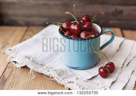 Fresh juicy sweet cherries in old rusty mug. Rustic wooden background with homespun napkin.
