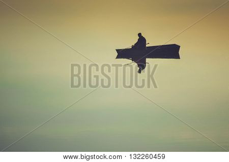 fisherman in a boat with his reflection in the mirrored water, filter or effect
