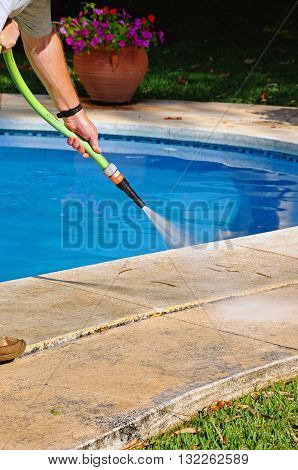 COSTA DEL SOL, SPAIN - OCTOBER 3, 2011 - Man hosing away leaves from the edge of a swimming pool Costa del Sol Andalucia Spain Western Europe, October 3, 2011.