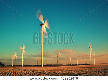 Wind Turbines Farm At Sunset In Spring