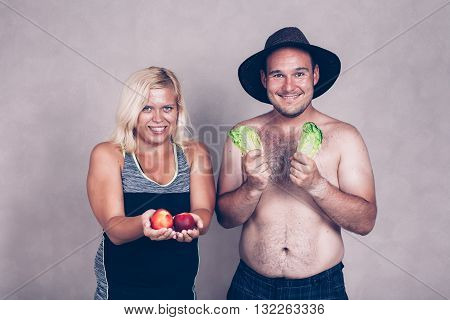 Funny young corpulent couple holding lettuce and nectarine.
