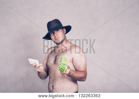 Naked corpulent man in hat holding pharmaceutical products and lettuce.