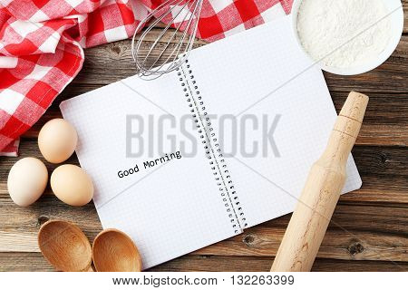 Open blank recipe book on brown wooden background, good morning