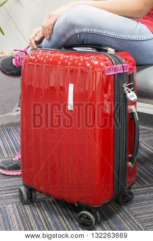 Passenger sitting and red travelling suitcase stock photo