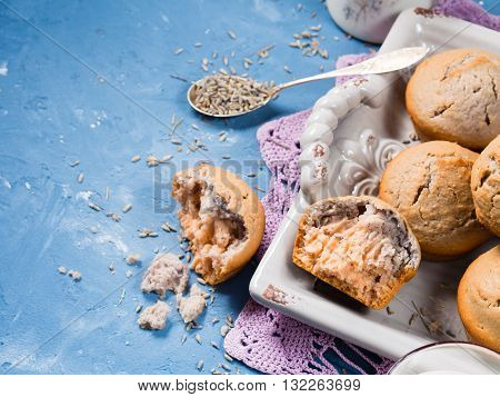 Lavender muffins with ingredients - lavender syrup milk and lavender flowers on blue textured background. Closeup. Copy space