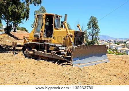 Yellow bulldozer parked on wasteland Costa del Sol Andalusia Spain Western Europe.