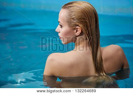 Young smiling woman enjoying water in the swimming pool at the hotel spa
