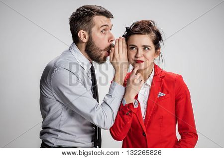 Young man telling gossips to his woman colleague at the office. Intrigues and wasting time concept