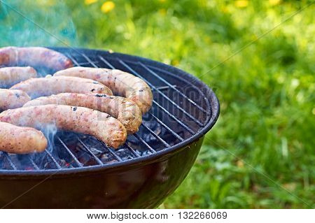 Cooking Pork Sausages on Barbecue Grill Outdoors