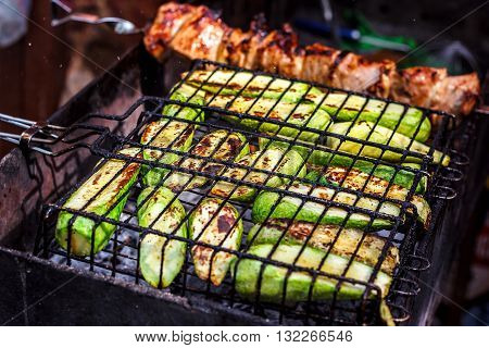 Fresh healthy green zucchini courgettes cucumber preparing on a barbecue grill over charcoal. Grilled zucchini slices. Vegetarian, Mediterranean cuisine. Delicious Food, vegetables on bbq party.