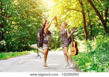 Two traveler women drinking beer and toast along the road through woods