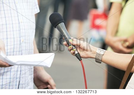 Reporter holding a microphone conducting an TV or radio interview