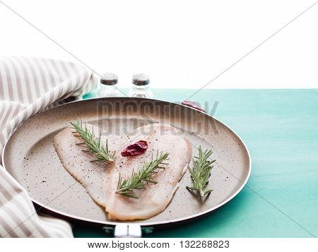 Heart shaped slice of chicken breast in a frying pan with red chilly pepper and rosemary herb on green pastel wooden background. Partly isolated on white