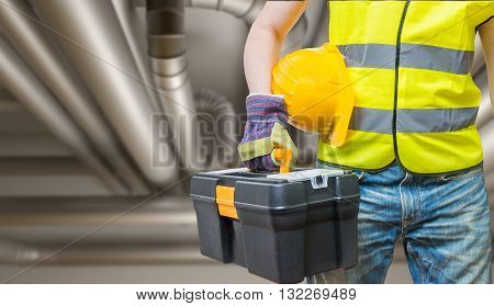 Industriual Concept. Worker With Tools And Pipelines In Backgrou