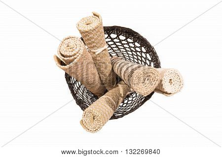 Hand-made short rolled carpets in dark rattan basket isolated on white background