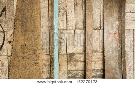 set of hand saw blade teeth on wooden parquet background