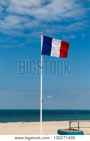 France flag on the mast and against blue ocean