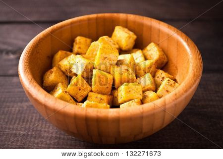 Bowl of fried tofu cubes with curry on wooden background. Close up