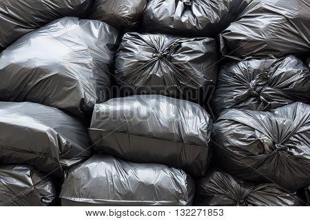 pile of plastic black garbage bags in daytime